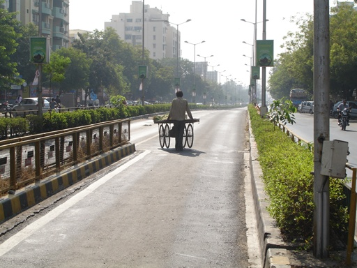 A street vendor entering the BRT lane, making an unsafe detour around the median to cross the road as the pedestrian crossing isn't wide enough for his cart.